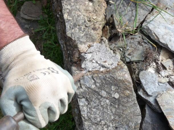 Eliminación do cemento da reconstrución que aparece ata a cimentación do muro.
